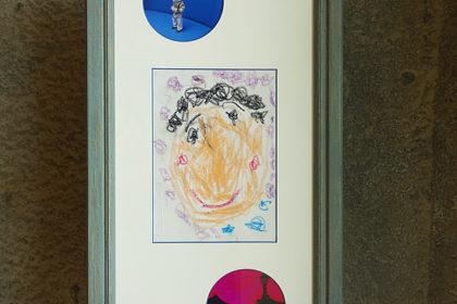 子供の描いた自画像と同時期の写真をひとつの額縁に飾る