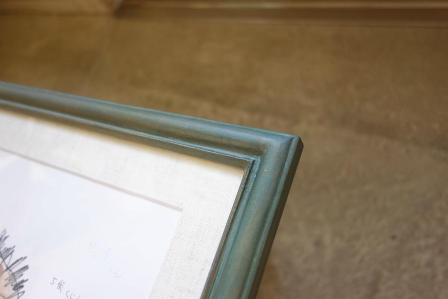 子どもの作品を飾る、淡い緑色の手彩色の額縁のコーナー部分の拡大写真